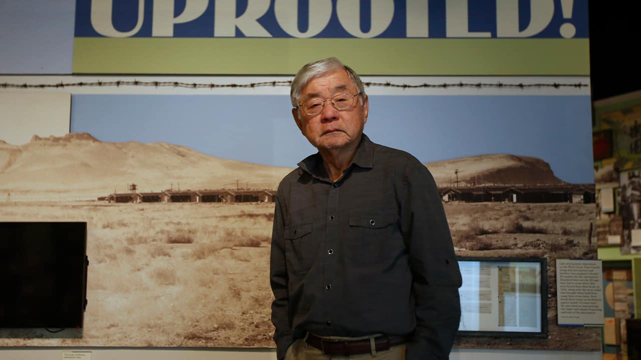 "Photo of Les Ouchida at the permanent exhibit titled ""UpRooted Japanese Americans in World War II"" at the California Museum in Sacramento"