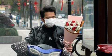 Photo of a man wearing a face mask carrying a bouquet
