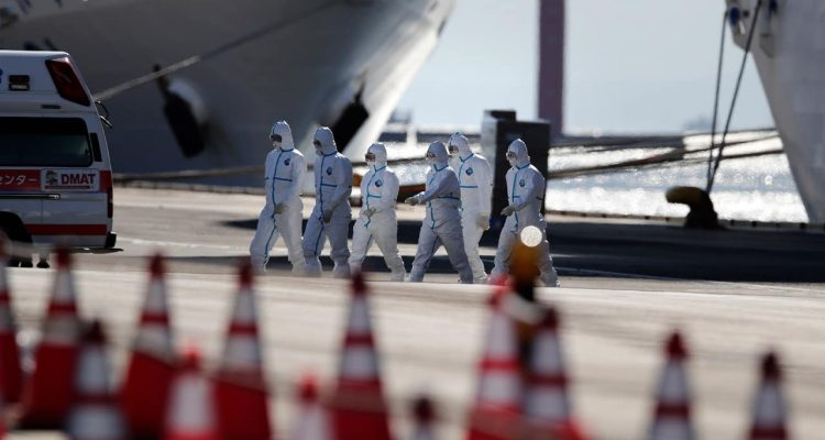 Photo of medical workers walking away from a quarantined cruise ship