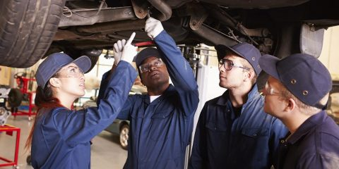 Photo of people in a shop class looking at a car