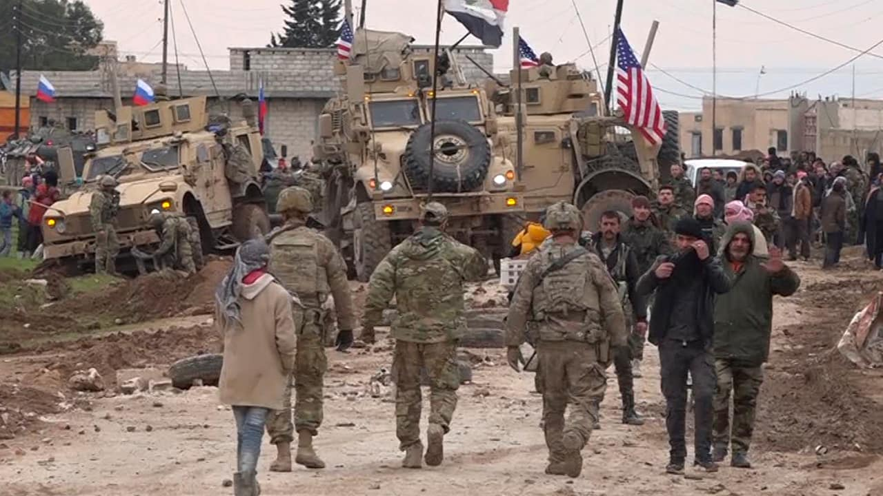 Photo of Russian, Syrian and others gather next to an American military convoy