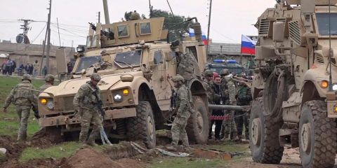 Photo of soldiers gathering next to an American military convoy