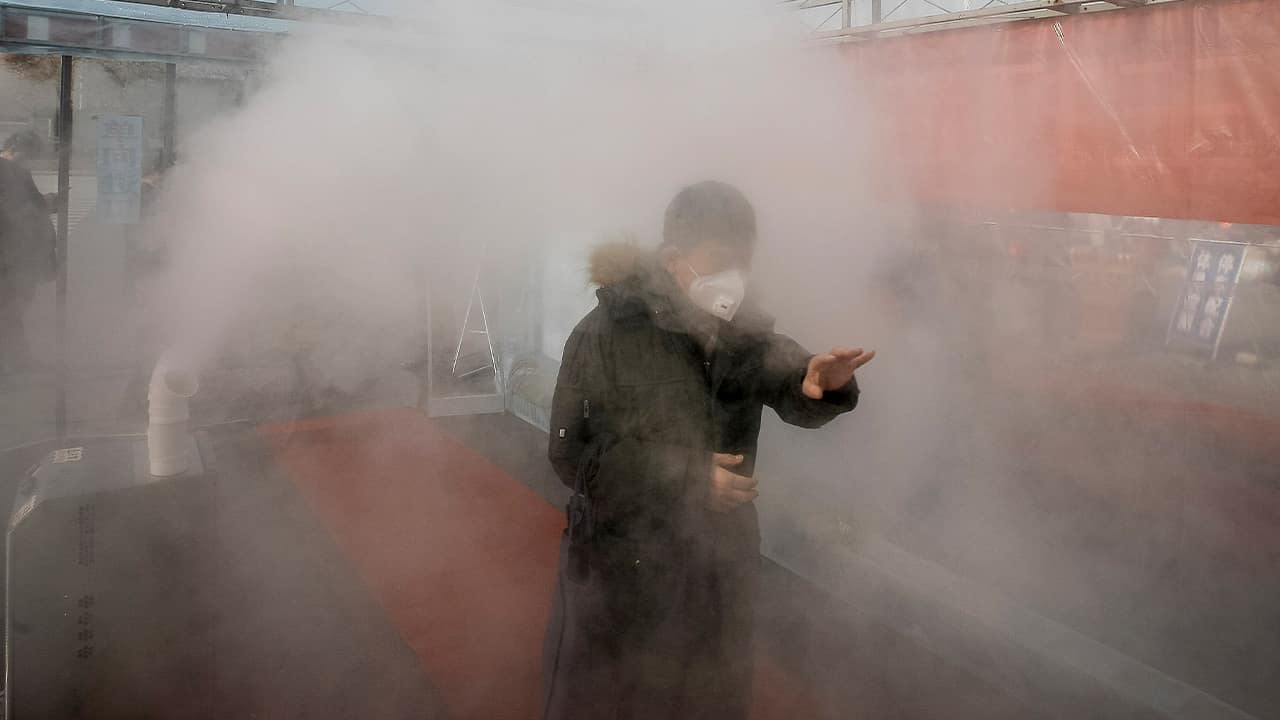 Photo of a man walking through a disinfectant spray in order to return home