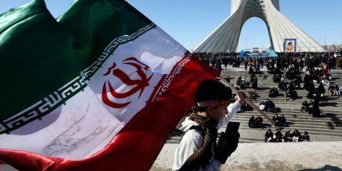 Photo of a boy carrying an Iranian flag