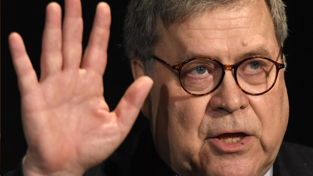 Photo of Attorney General William Barr putting his hand up