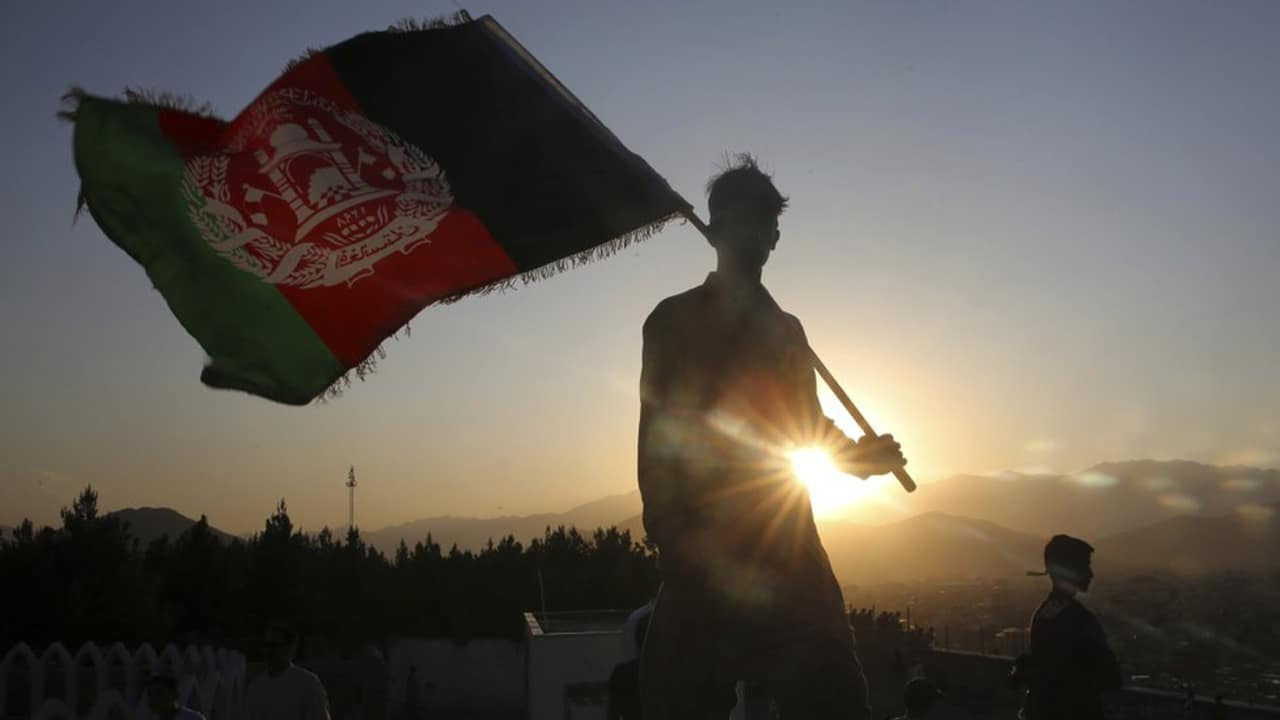 Photo of a man waving an Afghan flag in Kabul