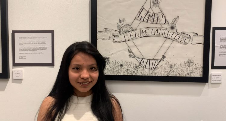 Photo of a Hoover High student in front of her artwork at M Street Street Arts Complex