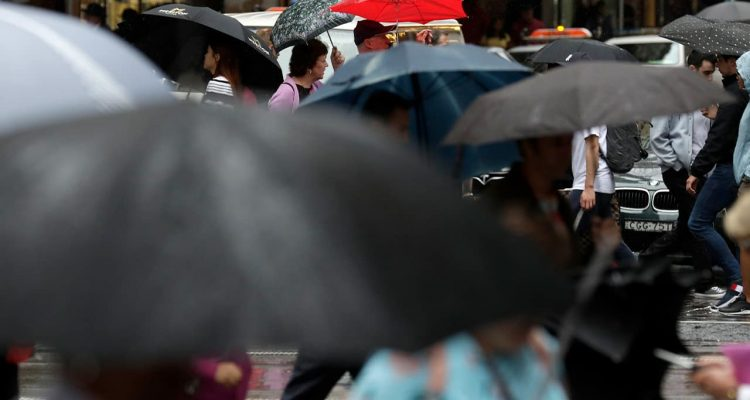 Photo of people sheltering under umbrellas in Australia