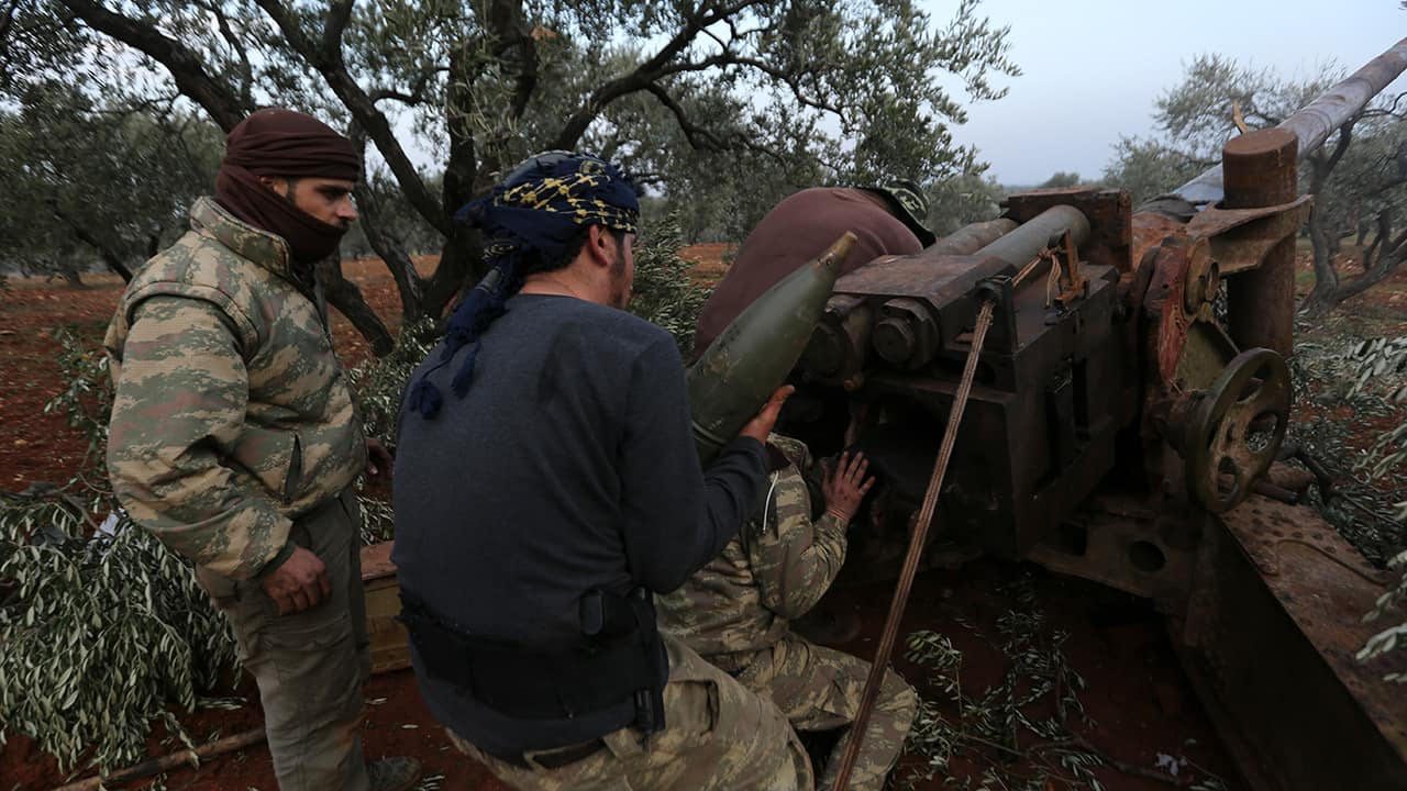 Photo of Syrian rebel fighters preparing to shoot a howitzer