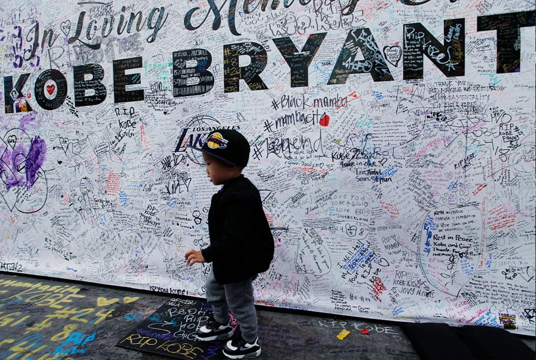 Photo of a boy walking by a standing board with messages for the late Kobe Bryant