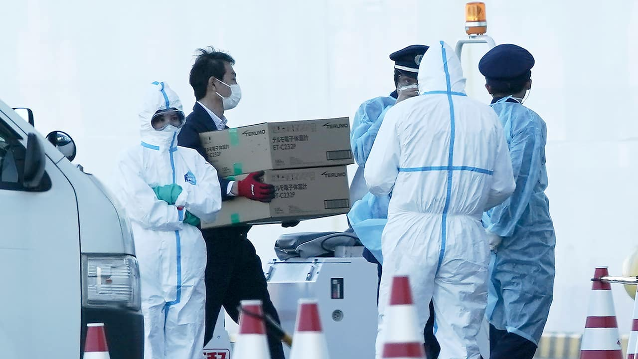 Photo of masked officials carrying boxes of digital thermometers
