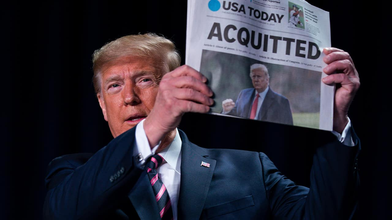"Photo of President Donald Trump holding up a newspaper that read ""ACQUITTED"""
