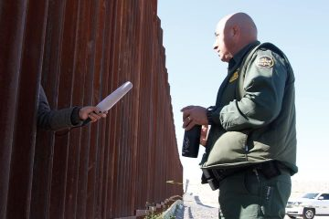 Photo of a journalist sticking her microphone through a through a border fence to interview a Border Patrol agent