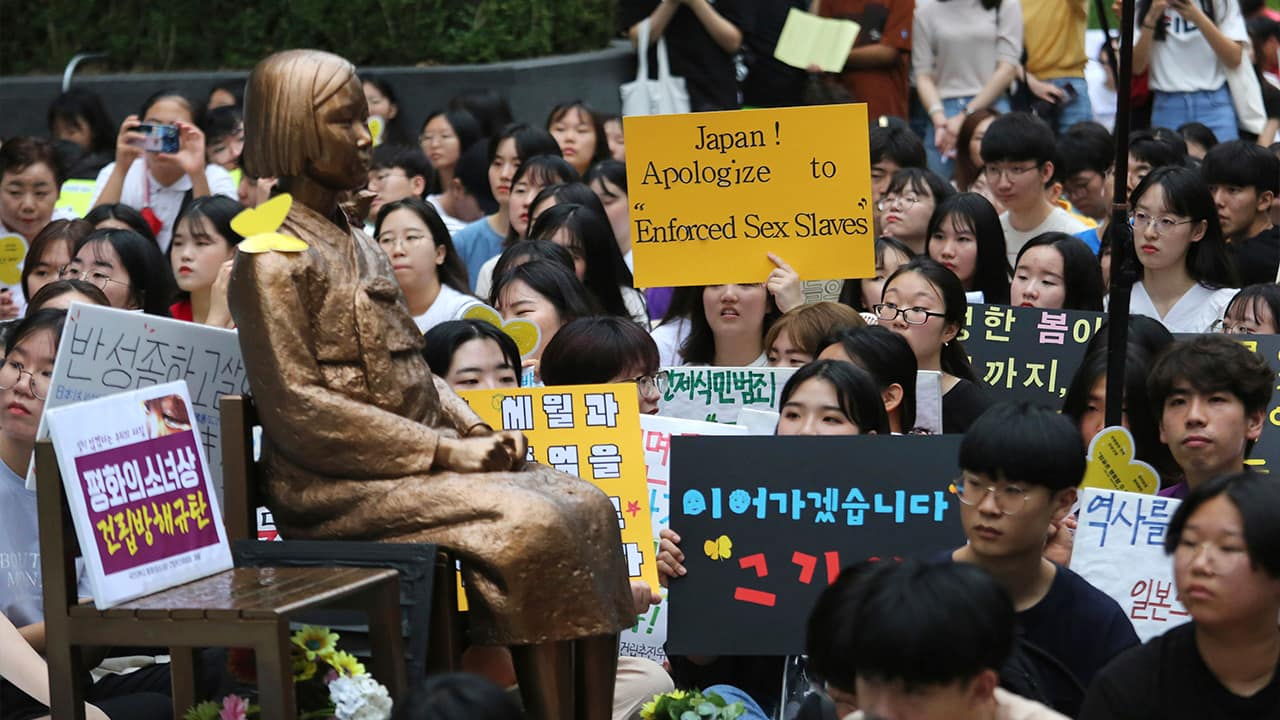 Photo of protesters staging a rally demanding full compensation and an apology for wartime sex slaves from Japanese government near a statue symbolizing sex slaves