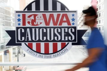 Photo of a pedestrian walking past an Iowa Caucuses sign