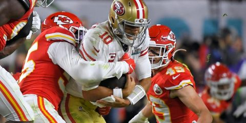 Photo of Kansas City Chiefs' Frank Clark, left, trying to tackle San Francisco 49ers' quarterback Jimmy Garoppolo