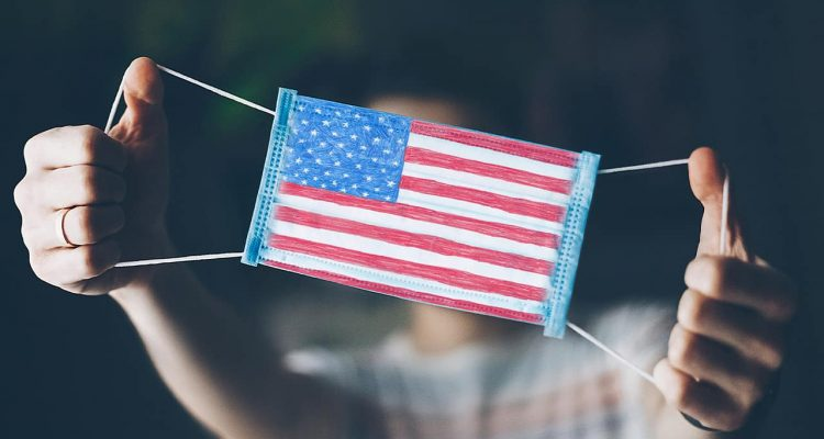 Photo of a man showing off a medical mask with an American flag on it