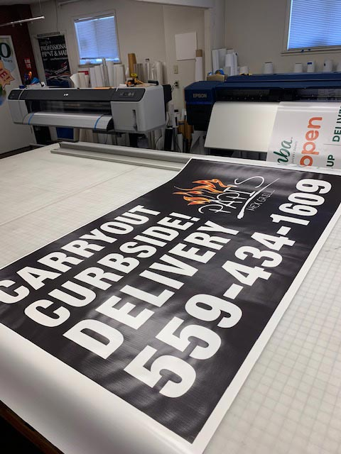 Photo of a banner being printed at Professional Print and Mail in Fresno, California