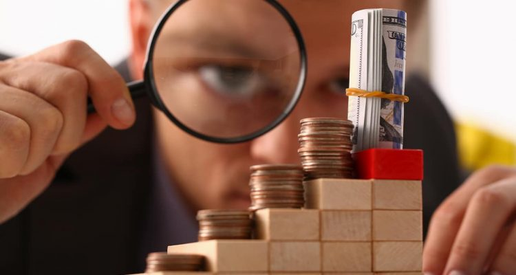 Photo of a man looking through a magnifying glass at small amounts of moneylas