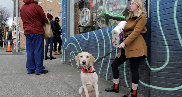 Photo of a woman and her dog waiting in line in Seattle