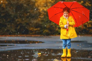 Picture of a young girl in yellow rain boots with a red umbrella