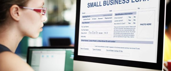 Photo of a woman looking at a small business loan form on a computer
