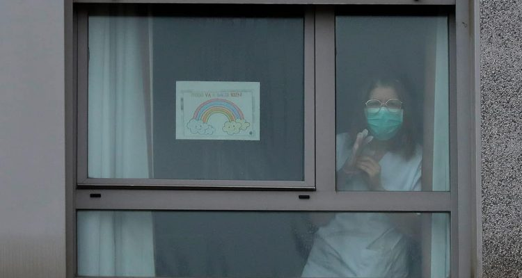 Photo of a nurse looking out the window of a nursing home