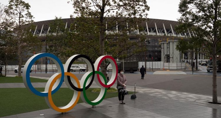Photo of a woman posing by the Olympics rings in Tokyo