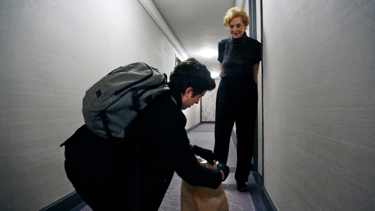 Photo of Liam Elkind delivering groceries to Carol Sterling