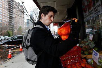 Photo of Liam Elkind looking at oranges