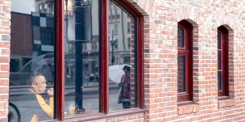 Photo of a man looking out the window of a restaurant