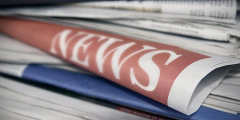 "Photo of newspapers stacked up with the word ""news"" showing"