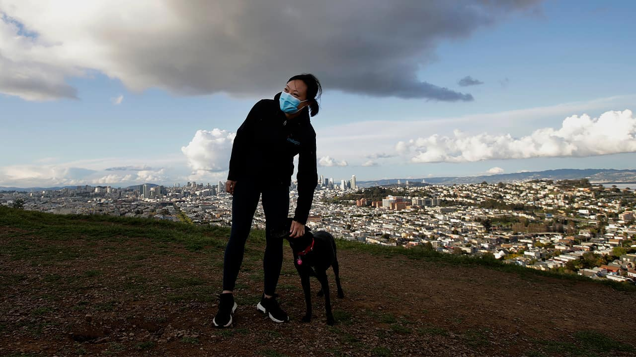 Photo of a woman wearing a mask while walking her dog