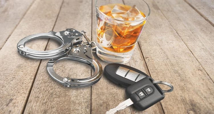 Photo of alcohol, keys and handcuffs symbolizing a drunk driving arrest