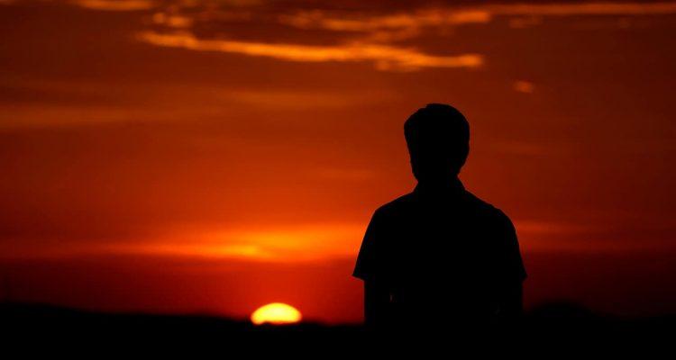Photo of a man watching a sunset