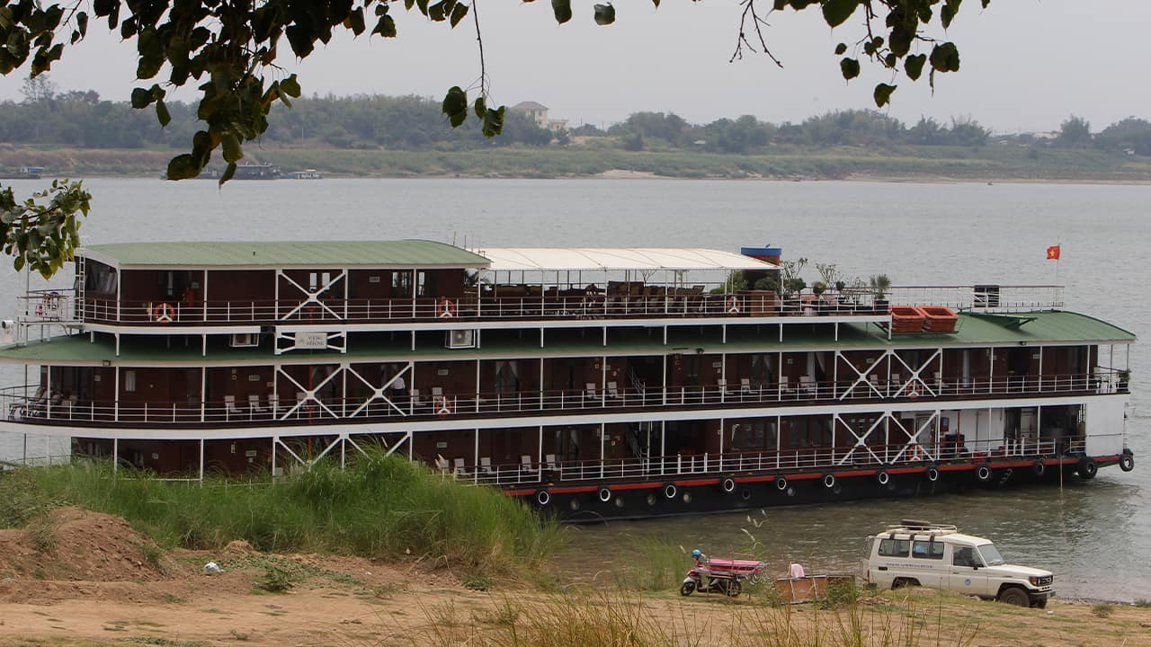 Photo of a cruise boat docked along the Mekong River bank in Kampong Cham, Cambodia