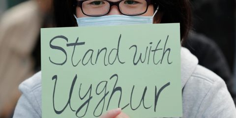 Photo of a man holding a sign during a rally to show support for Uighurs and their fight for human rights in Hong Kong