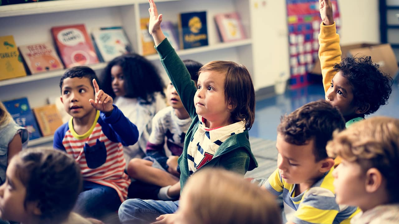 Photo of young students raising their hands in a classroom