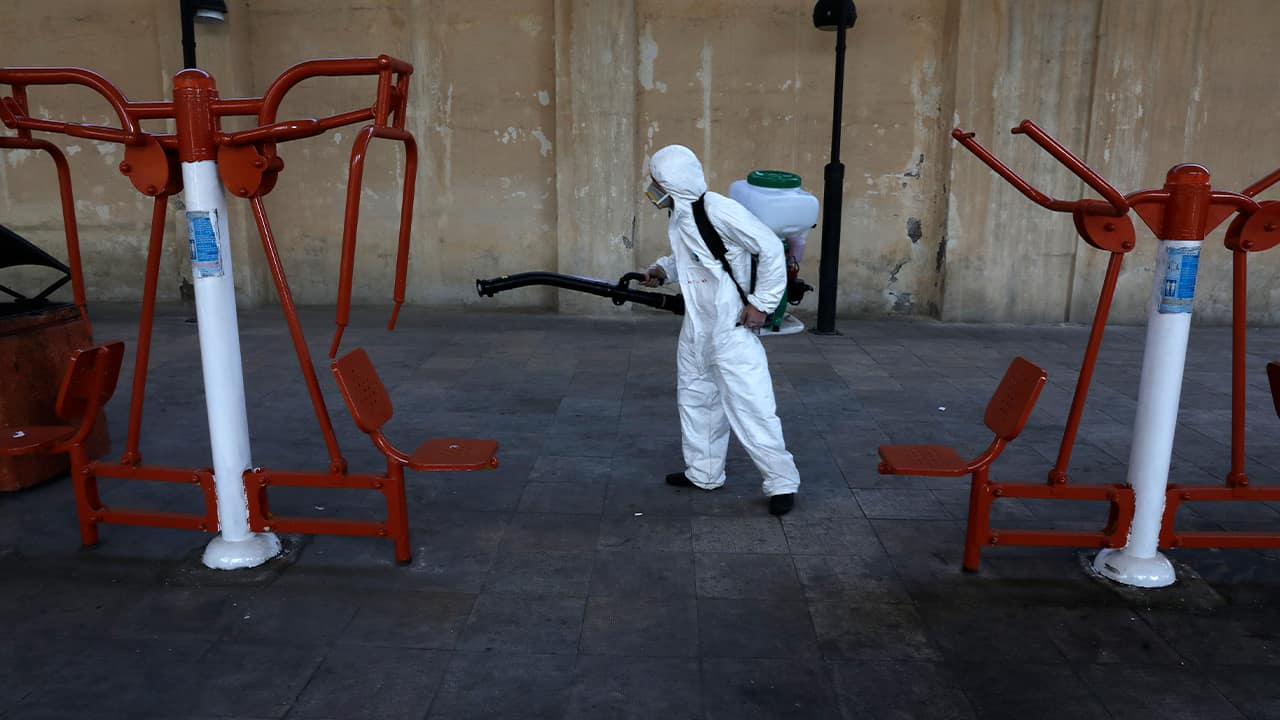 Photo of a firefighter disinfecting equipment in Tehran, Iran