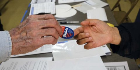 "Photo of someone being handed an ""I Voted"" sticker"