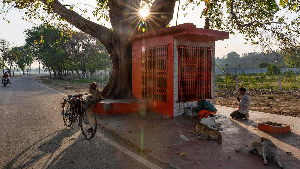 Photo of people outside a roadside Hindu temple in India