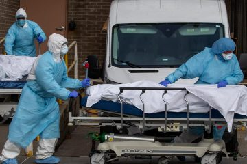 Photo of health care workers removing bodies