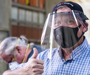 Photo of a man wearing a face shield that he made giving the thumbs-up sign