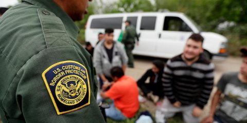 Photo of a border patrol agent talk to a group of people