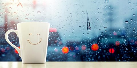 Photo of a happy face mug with rain droplets in the background