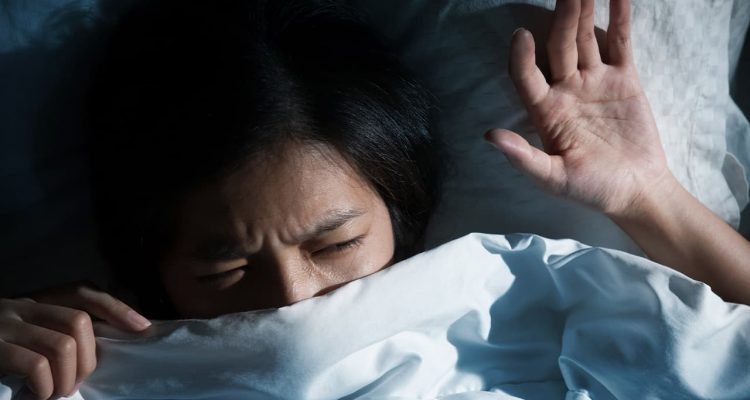 Photo of a girl waking up from a bad dream
