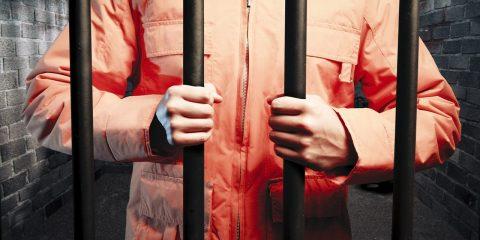 Photo of inmate in orange jumpsuit behind bars