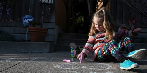 Photo of a young girl drawing with chalk