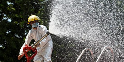Photo of a firefighter spraying disinfectant