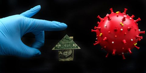 Image of a gloved hand, a dollar bill folded into the shape of a house, and coronavirus symbolizing challenges of paying rents and mortgages during the pandemic